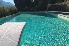 piscina a sfioro a cascata su un lato con zona tuffi
